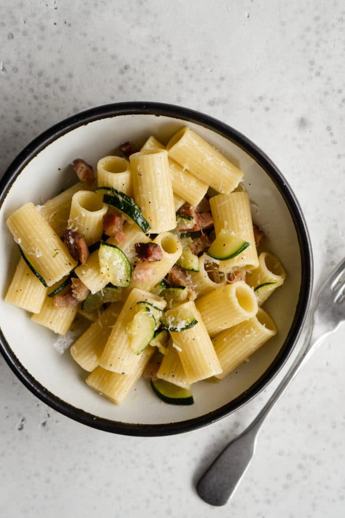 Zucchini and pancetta pasta in a bowl with a fork to the side