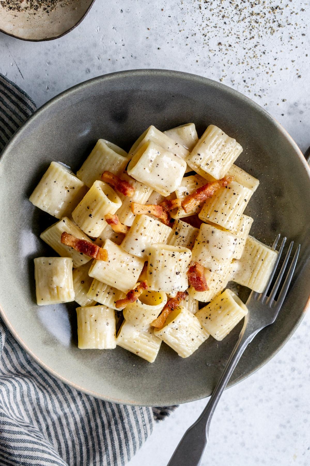 Pasta alla gricia in a gray bowl on a napkin