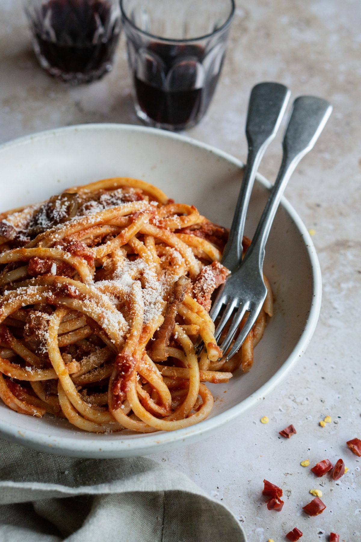 Pasta amatriciana in a bowl with glasses of red wine in the background