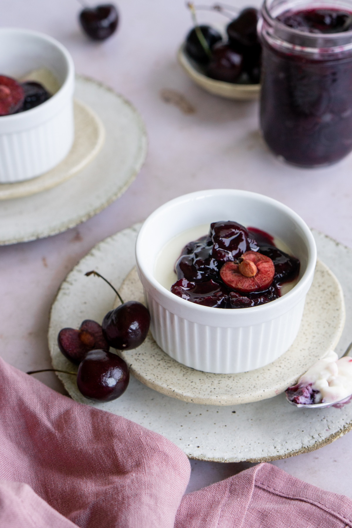 Italian panna cotta in a ramekin surrounded by fresh cherries and a pink napkin