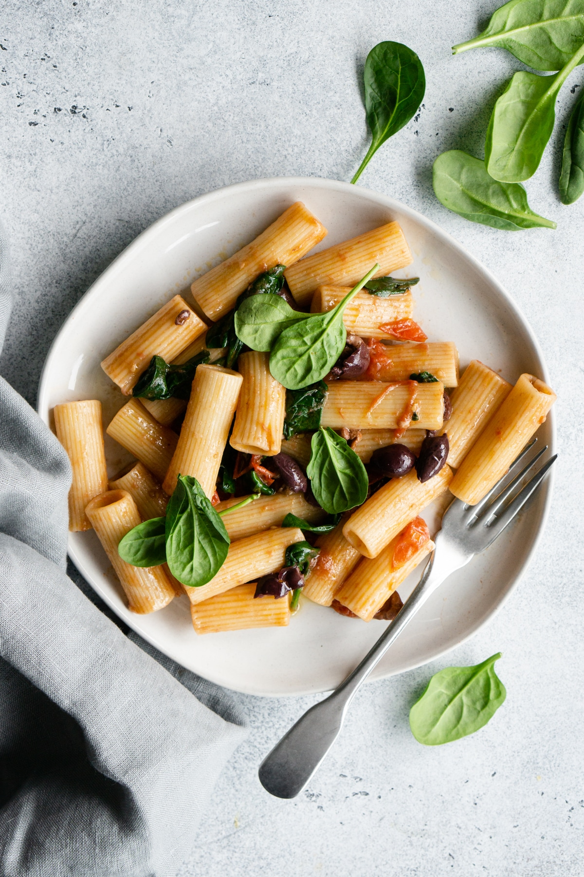 Spinach penne pasta in a plate with a fork