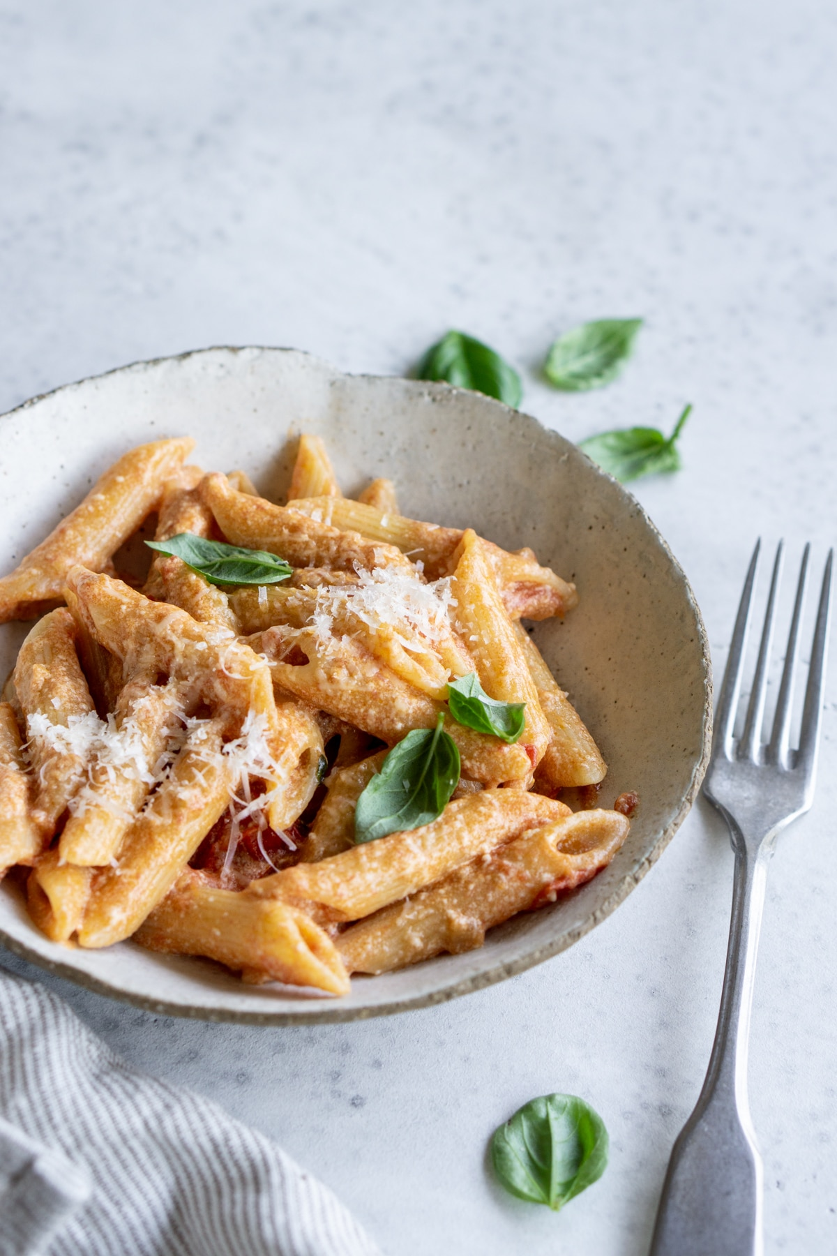 Tomato ricotta pasta in a plate topped with fresh basil