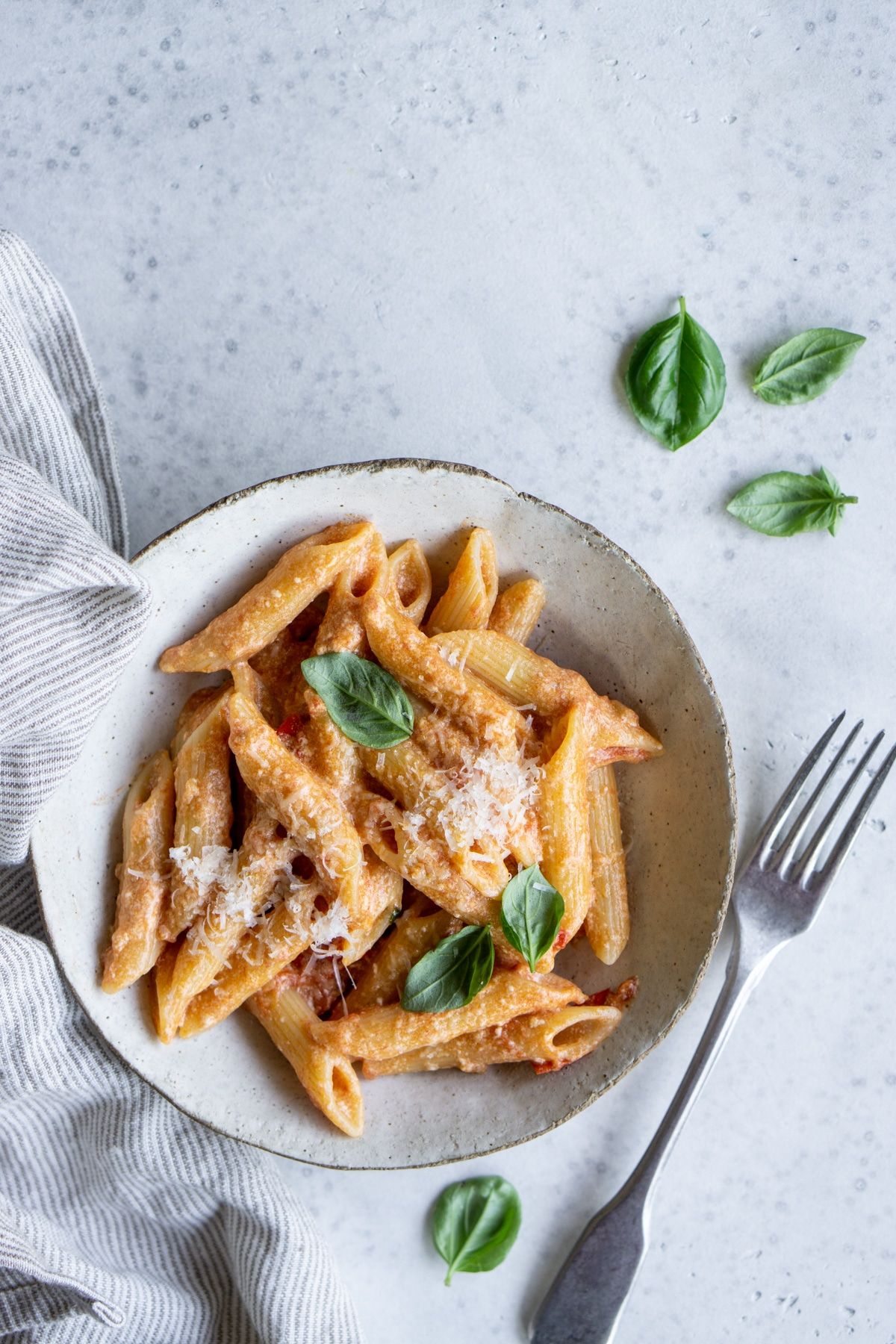 Bowl of tomato ricotta pasta with a napkin to the side